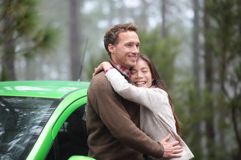 Couple driving in green car in love on travel. Happy drivers in new rental car on vacation holidays road trip resting in forest embracing and hugging in royalty free stock images