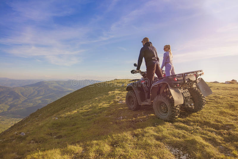 Couple driving off-road with quad bike or ATV royalty free stock images
