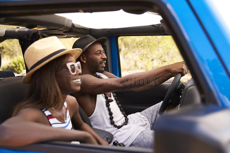 Couple Driving Open Top Car On Country Road royalty free stock images