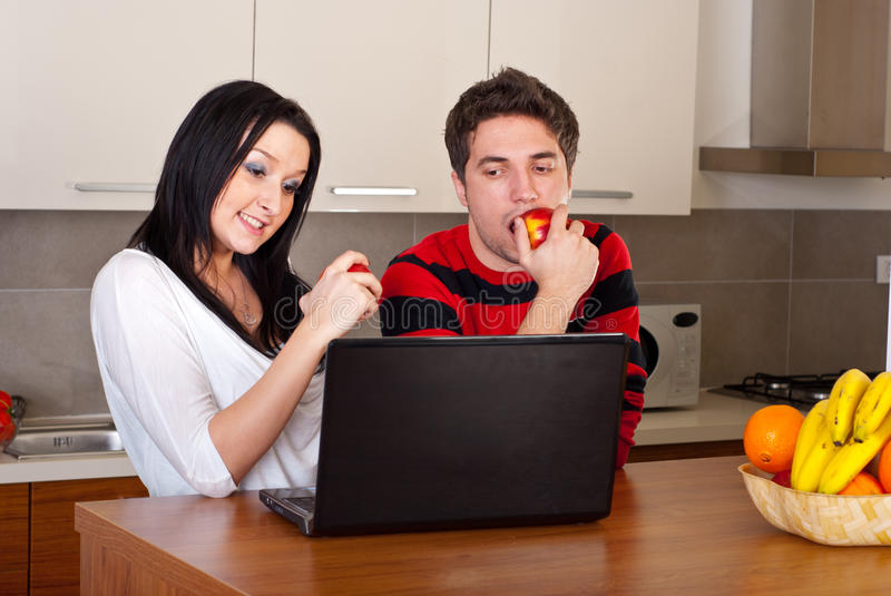 Couple eating apples and using laptop stock photos