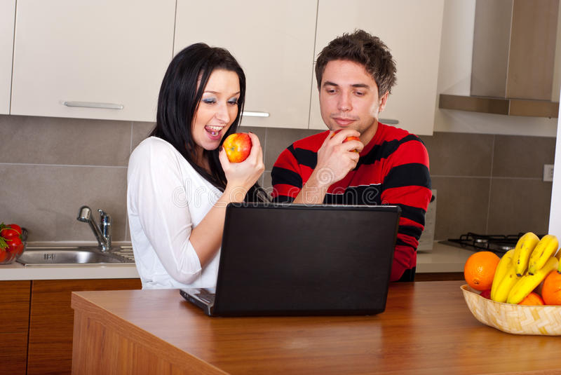 Couple eating apples and using laptop in kitchen royalty free stock photography