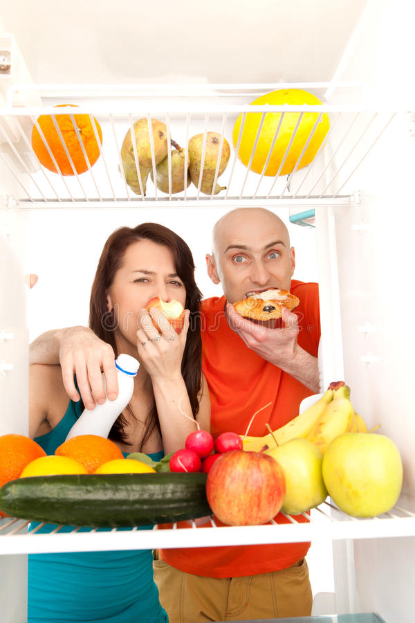 Couple eating cakes. A couple eating cream cakes standing in the open door of the refrigerator full of healthy fresh fruit royalty free stock image