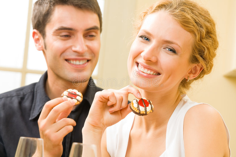 Couple eating cakes at home. Happy couple eating cakes at home. Focus on woman royalty free stock images