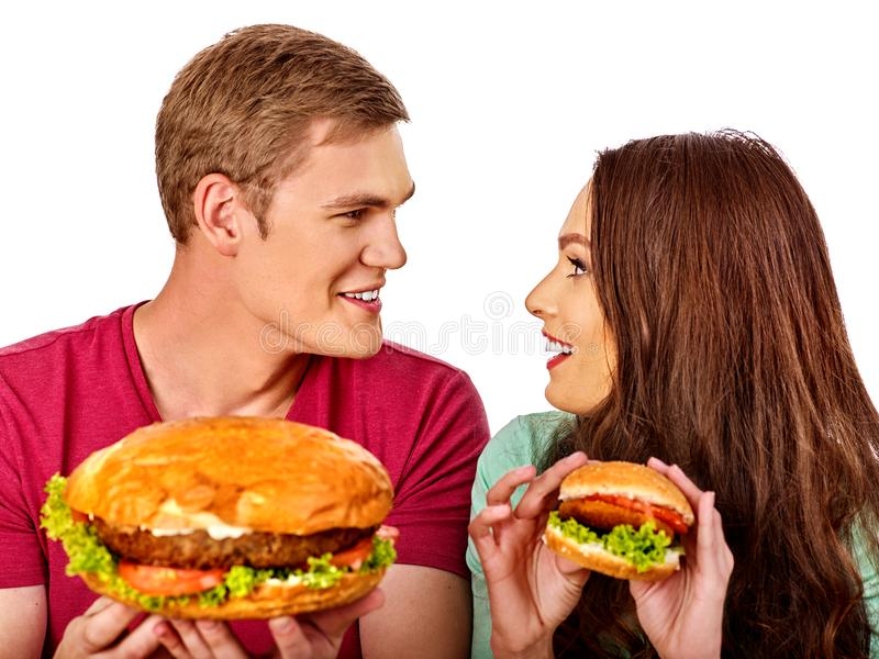 Couple eating fast food. Man and woman eat hamburger with ham. Friends holding burders junk on isolated. Loving couple prefers fast food to homemade dinner stock image