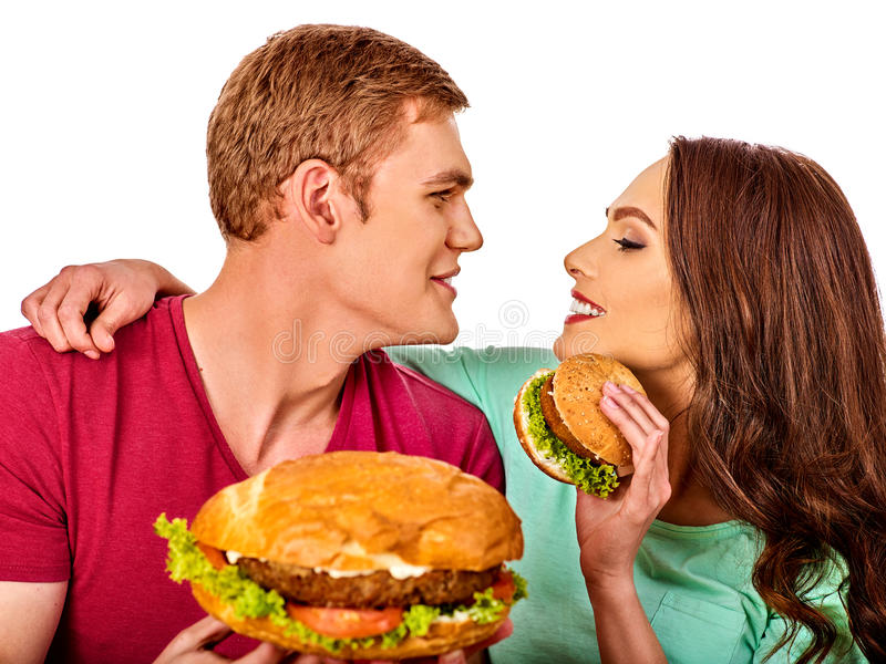 Couple eating fast food. Man and woman eat hamburger with ham. Couple eating fast food. Man and women eat hamburger with ham. Friends holding burders junk on stock photo