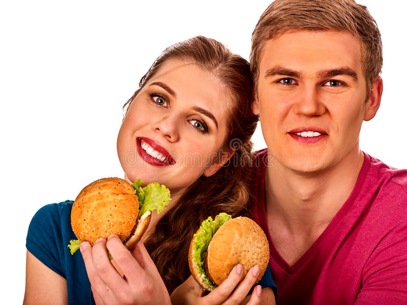 Couple eating fast food. Man and woman eat hamburger. Couple eating in fast food restaurant. Man and women eat hamburger with ham . Friends holding two burder stock photo