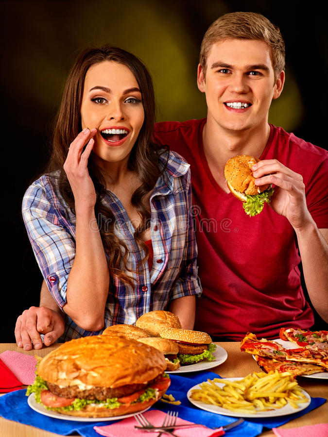 Couple eating fast food. Man and woman eat hamburger. Couple eating fast food. Man and women eat hamburger with ham. Friends holding two burder junk on dark stock photography