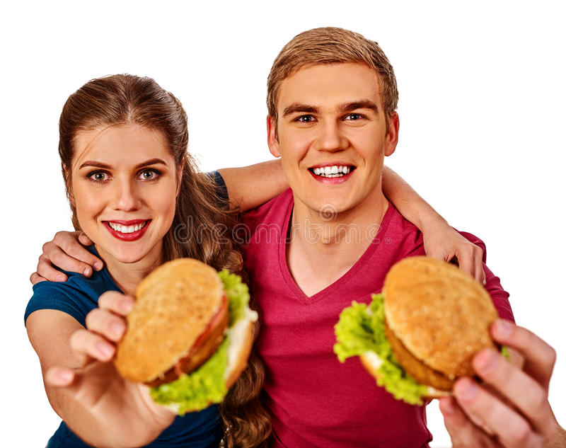 Couple eating fast food. Man and woman eat hamburger. Couple eating fast food. Man and women eat hamburger with ham . Friends holding two burder junk on white stock photos