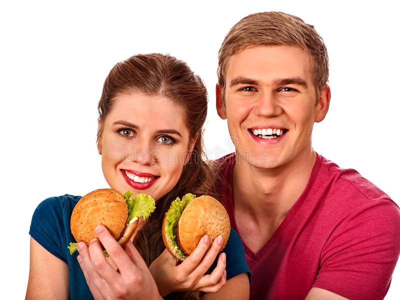 Couple eating fast food. Man and woman eat hamburger. Couple eating fast food. Man and women eat hamburger with ham. Friends holding two burder junk on white royalty free stock image