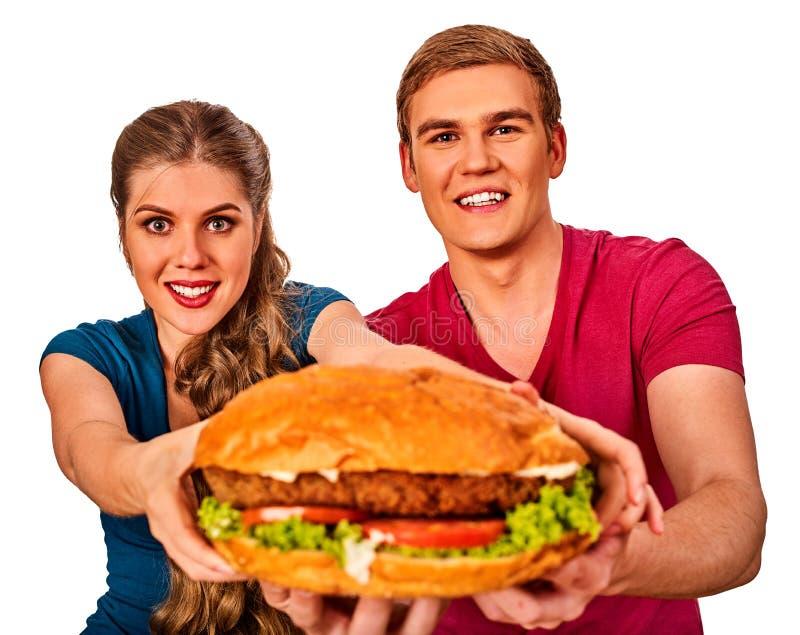 Couple eating fast food. Man and woman treat hamburger . stock photo