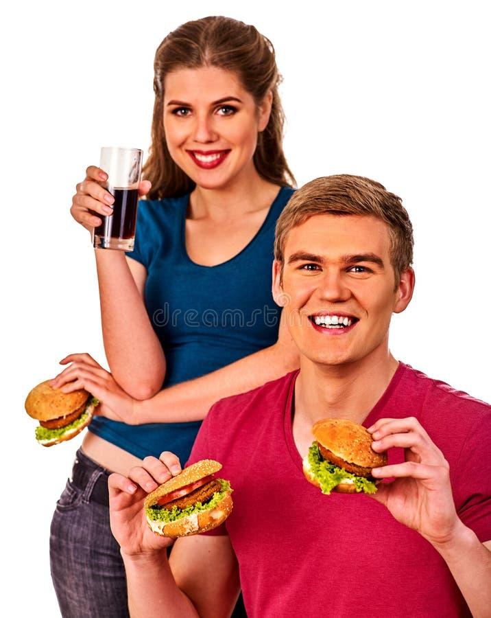 Couple eating fast food. Man and woman treat hamburger . stock photos