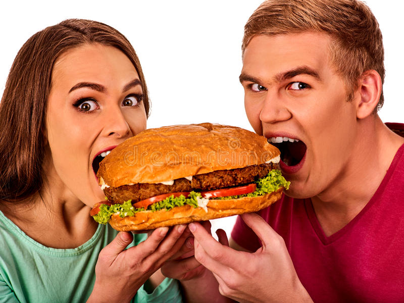 Couple eating fast food. Man and woman treat hamburger . royalty free stock images
