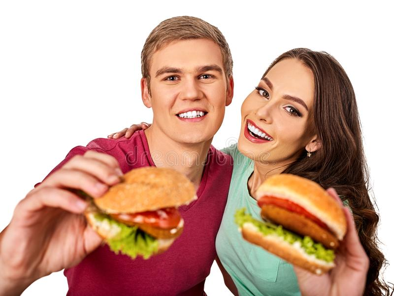 Couple eating fast food. Man and woman eat hamburger. Couple eating fast food. Man and women eat hamburger with ham. Friends holding two burder junk on white stock images