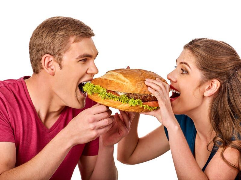 Couple eating fast food. Man and woman treat hamburger . royalty free stock image