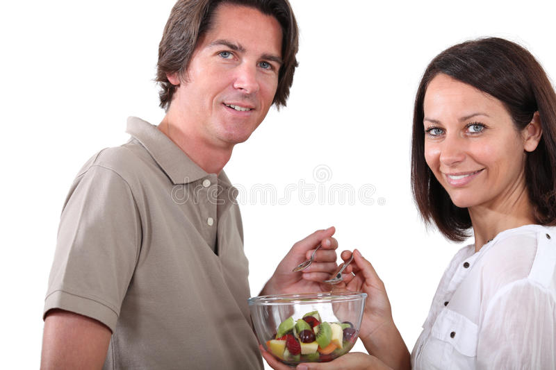 Couple eating fruit salad royalty free stock images