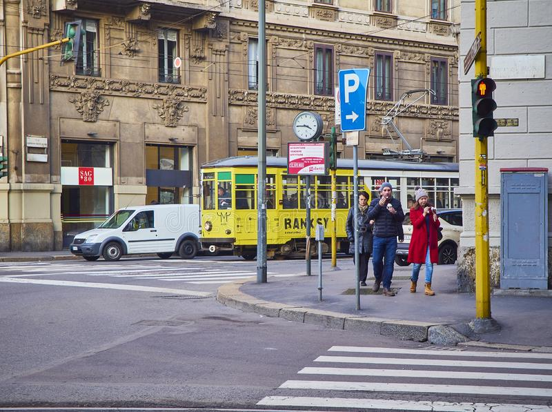 A couple eating Ice cream in front of a tram crossing a street of Zona Magenta neighborhood. Milan, Italy. Milan, Italy - December 29, 2018. A couple eating Ice royalty free stock photo