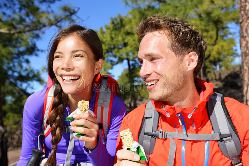 Couple eating muesli bar hiking happy. Couple eating muesli bar hiking. Happy people enjoying granola cereal bars living healthy active lifestyle in mountain stock photography