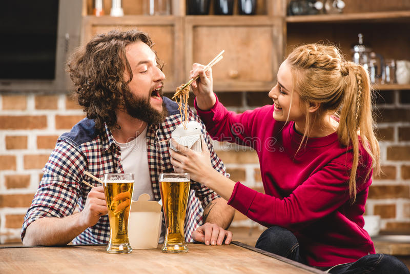 Couple eating noodles. Happy couple eating noodles with chopsticks royalty free stock photos