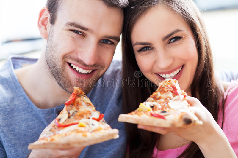 Couple eating pizza. Smiling young couple eating pizza