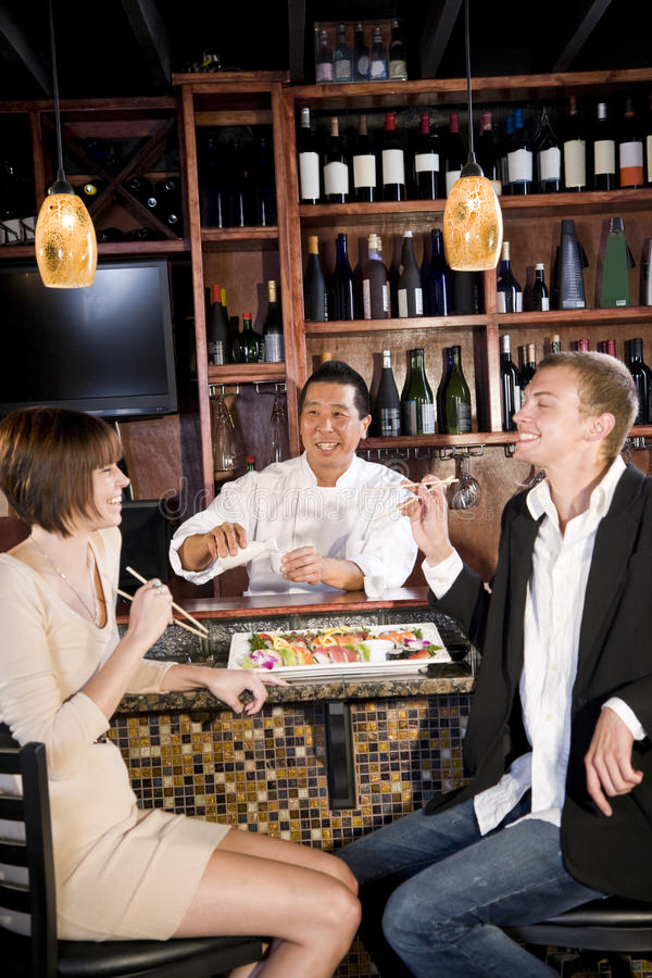 Couple eating sushi in Japanese restaurant. Sushi chef serving young couple in Japanese restaurant stock images
