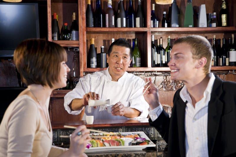 Couple eating sushi in Japanese restaurant. Sushi chef serving young couple in Japanese restaurant royalty free stock photos