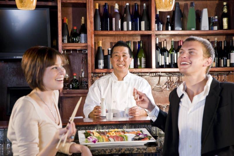 Couple eating sushi in Japanese restaurant. Sushi chef serving young couple in Japanese restaurant stock photos