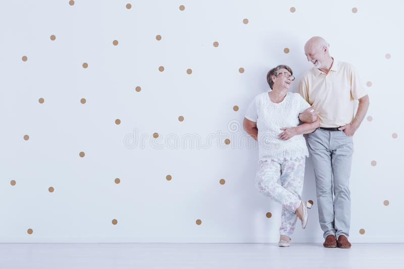 Couple of elders. Leaning against the wall with dots and looking into each other`s eyes stock image