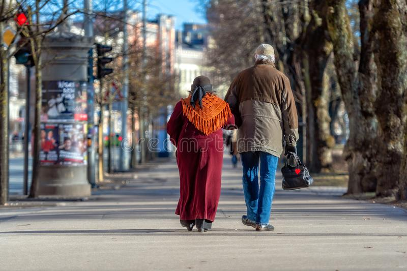 A couple of eldery people in hands are walking through the city street. Rear view royalty free stock photos