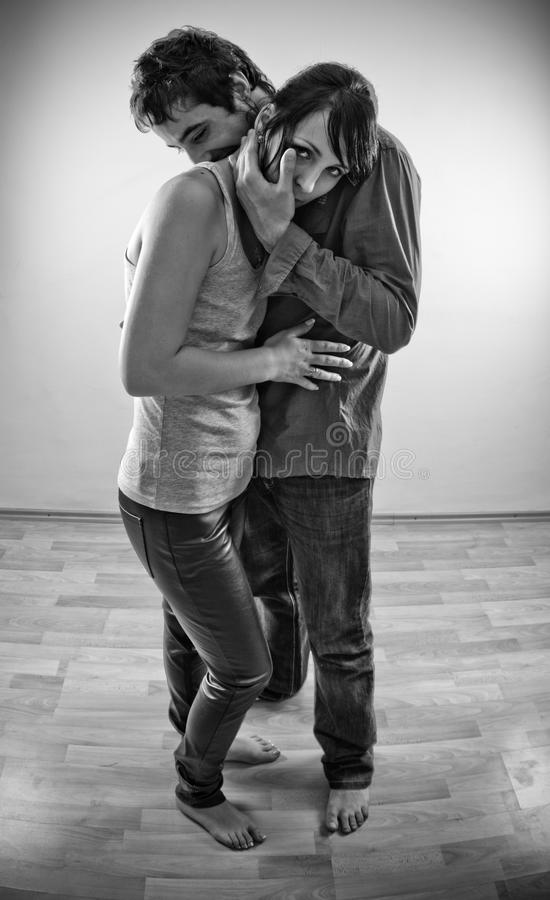 Couple embrace. Beautiful young couple holding each other in an embrace royalty free stock image