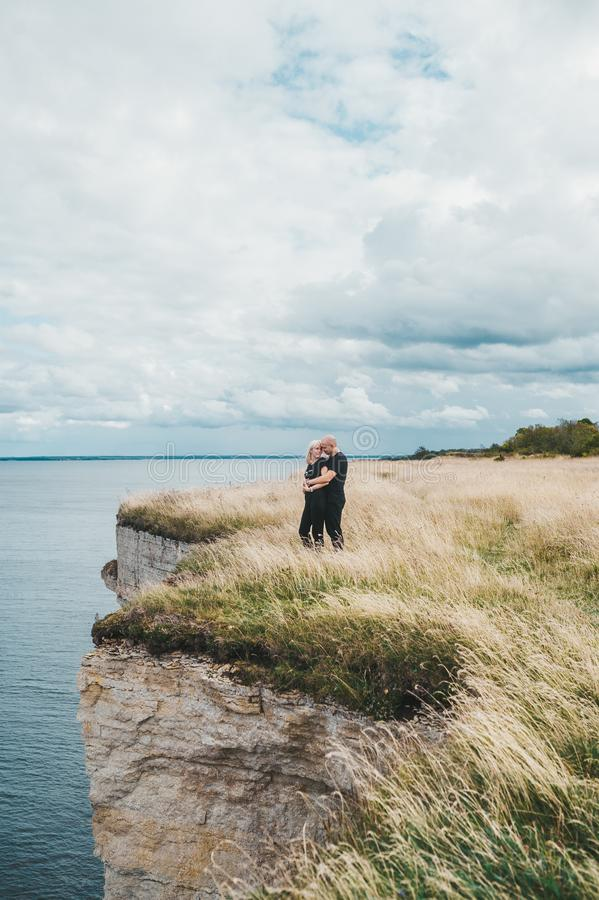 A couple embrace on grass on the edge of the rocky coast of the Baltic sea royalty free stock images