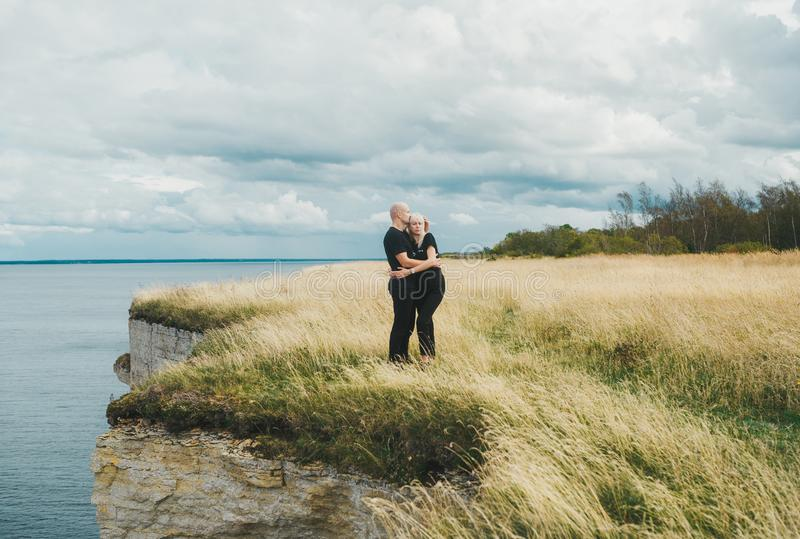 A couple embrace on grass on the edge of the rocky coast of the Baltic sea stock photography