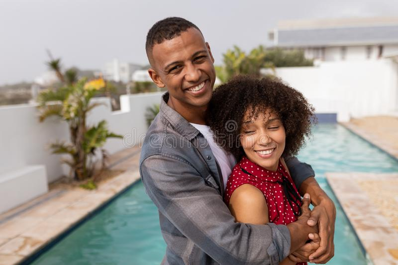 Couple embracing each other near swimming pool at home. Front view of happy mixed-race couple embracing each other near swimming pool at home. They are smiling royalty free stock image