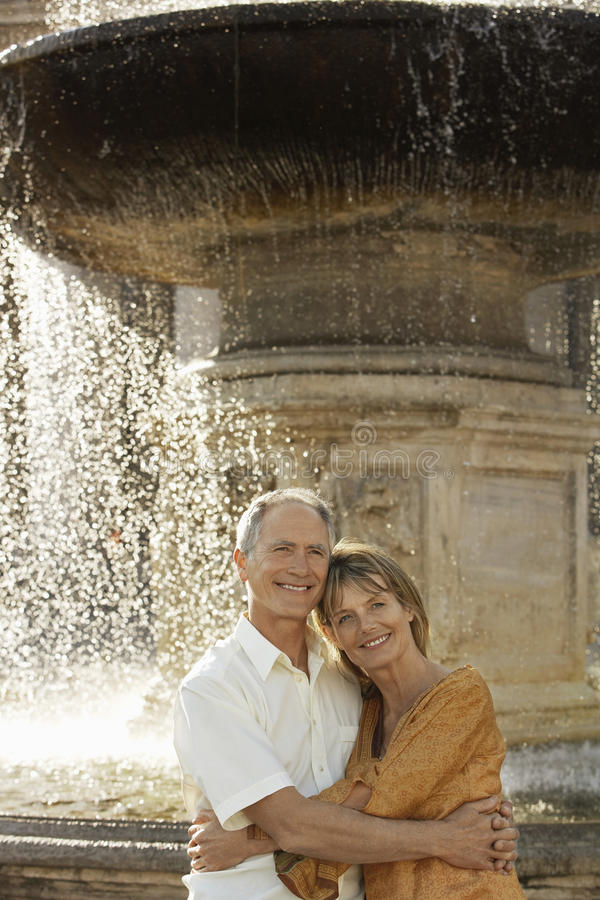 Couple Embracing By Fountain stock image