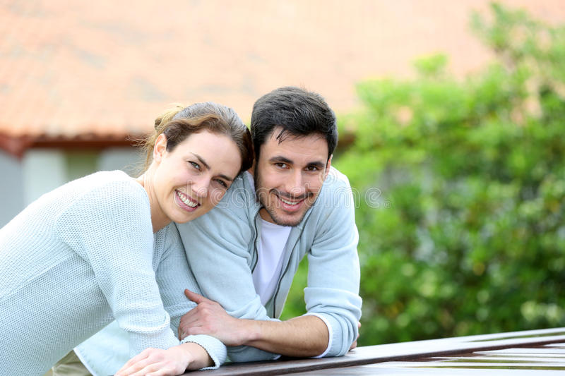 Couple embracing in front of the house. Couple embracing each other in front of house stock images