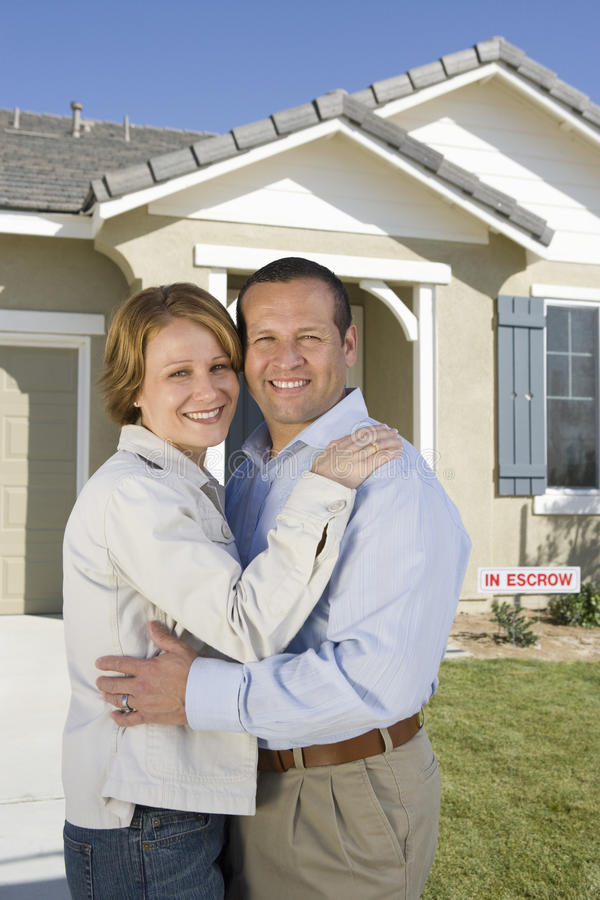Couple Embracing In Front Of New House. Portrait of happy mature couple embracing in front of new house stock photography