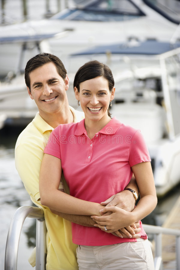 Couple embracing at harbor. Portrait of Caucasian mid-adult couple embracing at harbor royalty free stock image