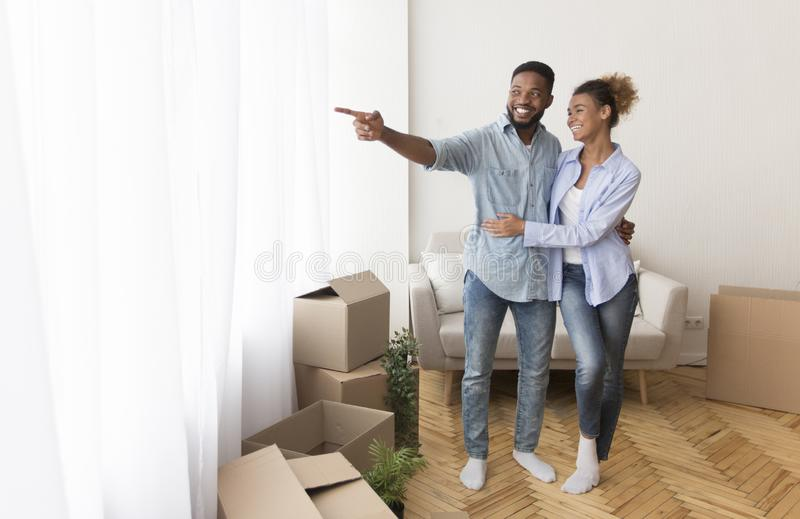 Couple Embracing Looking At Window View After Relocation In Apartment royalty free stock images