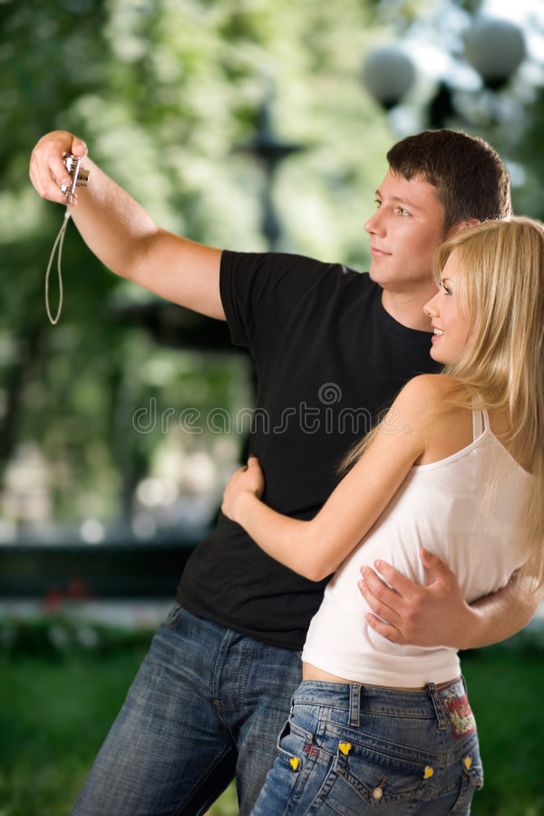 Couple embracing outdoors and taking photograph royalty free stock photo