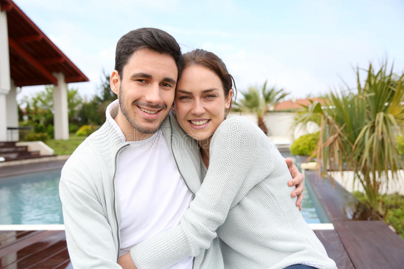 Couple embracing by the pool. Couple embracing each other in front of house stock image