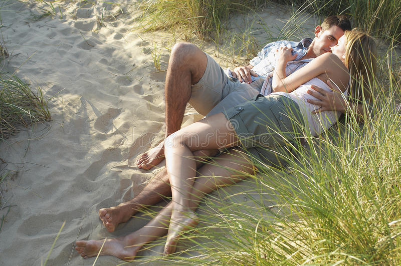 Couple Embracing In Secluded Spot At Beach. Young couple lying and embracing in secluded spot at beach stock photos