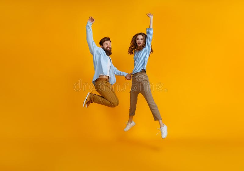 Couple of emotional people man and woman jumping on yellow background stock photos