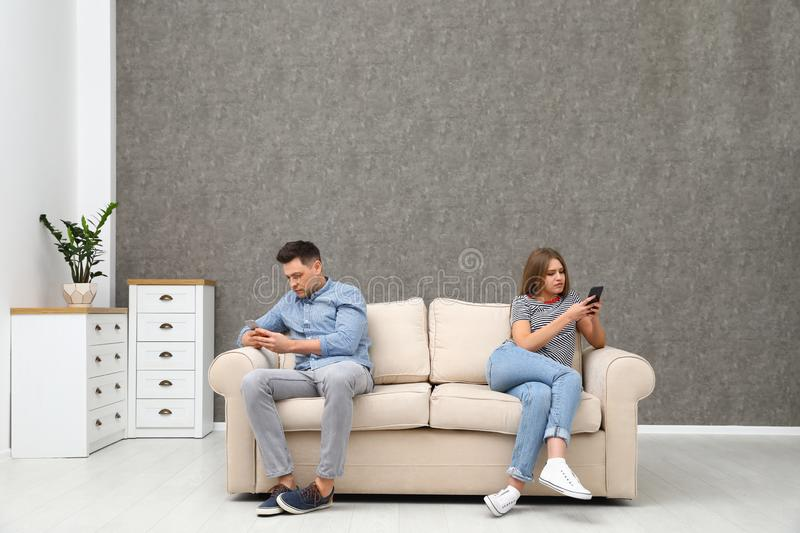 Couple engaged in smartphones while spending time together. Loneliness concept stock images