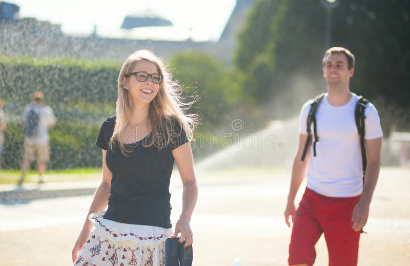 Couple enjoing water spray on a hot day royalty free stock images