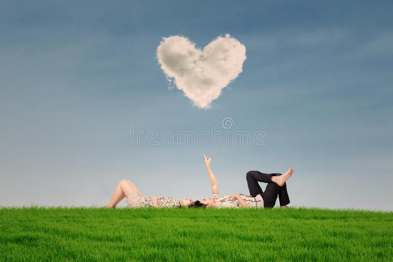 Couple Enjoy Holiday Under Heart Cloud In Park Stock Images