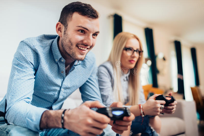Couple enjoying computer video games with game console. Details of modern lifestyle. Attractive male and woman playing royalty free stock images
