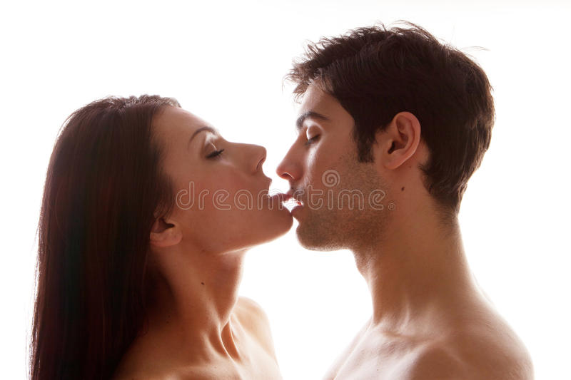 Couple Enjoying Erotic Kiss. Both in profile with the women extending her togue to touch the mens mouth stock photography