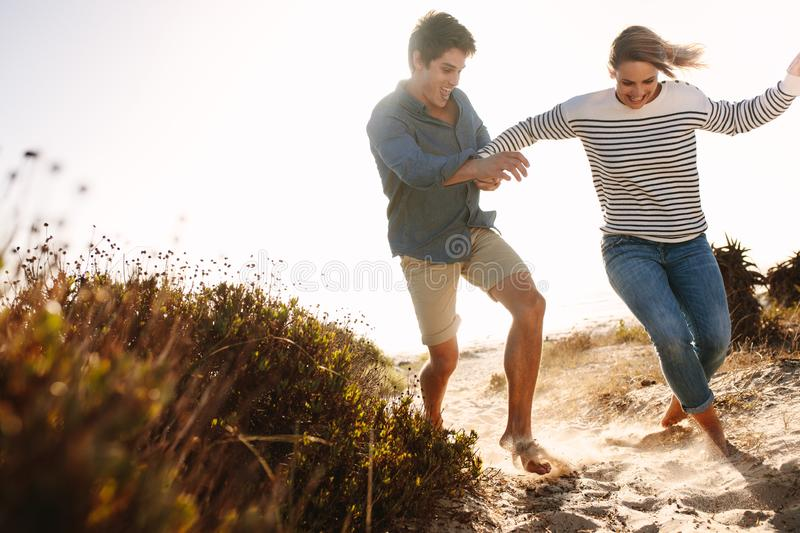 Couple enjoying and having fun on the beach. Happy men and women running on the beach having fun. Couple playing and running in the sand near sea shore on a royalty free stock image