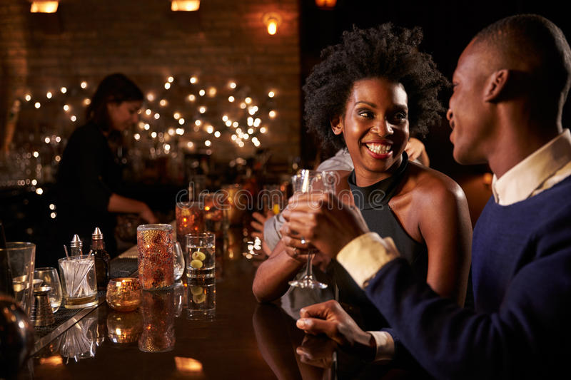 Couple Enjoying Night Out At Cocktail Bar stock image