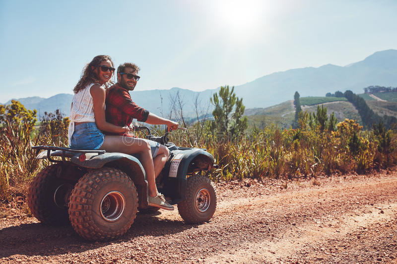 Couple enjoying a quad bike ride in countryside royalty free stock photos