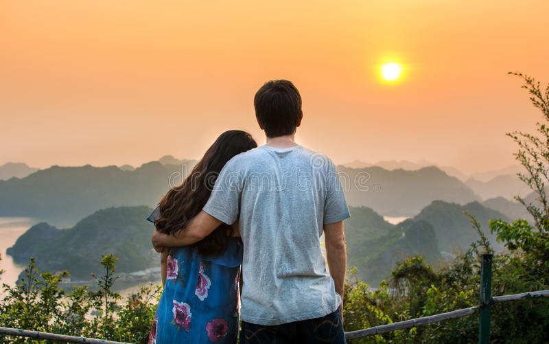 Couple enjoying romantic sunset at viewpoint royalty free stock image